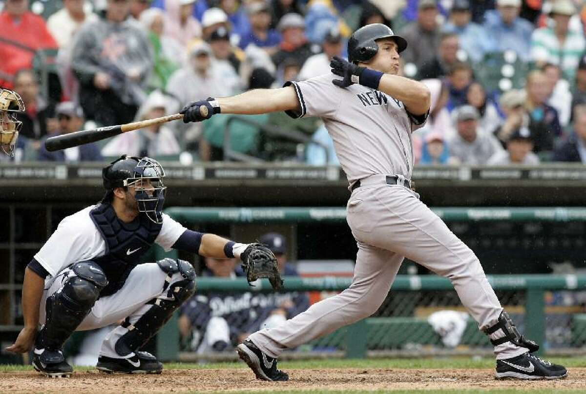 ASSOCIATED PRESS New York Yankees' Mark Teixeira hits a solo home run as Detroit Tigers catcher Alex Avila, left, watches in the eighth inning of Thursday's game in Detroit. The Yankees won 4-3.