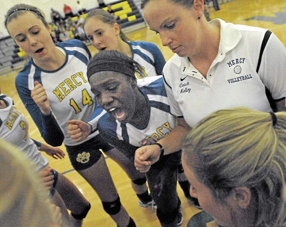Mercy seniors Mackenzie Dougan, Jessica Hoops and junior Shy Williams in a time-out huddle with Coach Sarah Kelley shortly before their final set against Foran. Mercy won all three games, 25-17, 25, 14, 25-23 Monday night at home. Photo: Catherine Avalone — The Middletown Press  / TheMiddletownPress