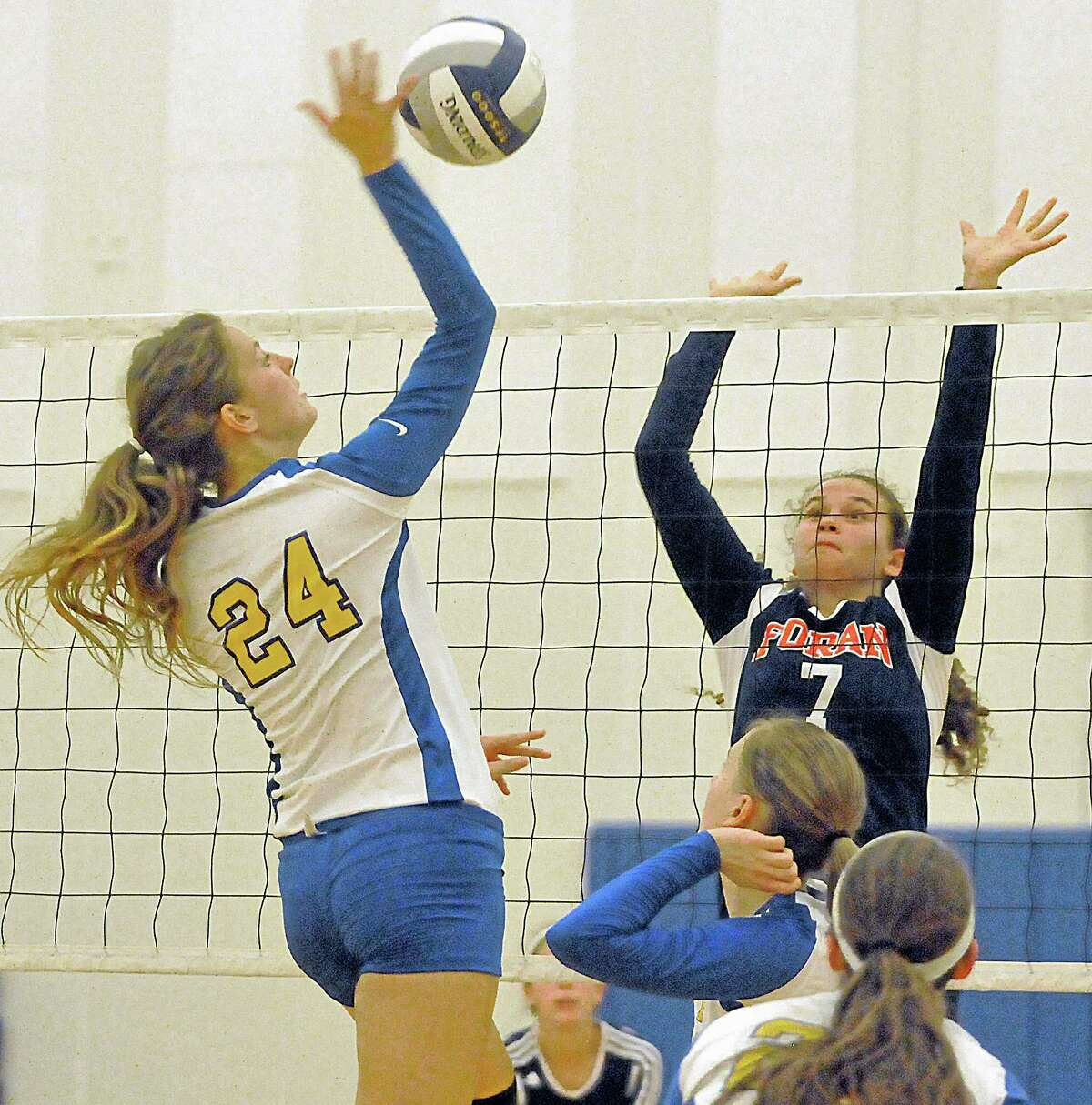Mercy senior Morgan Cahill spikes the ball at Foran's Janae Owen in the second set against Foran. Mercy won all three games, 25-17, 25, 14, 25-23 Monday night at home.