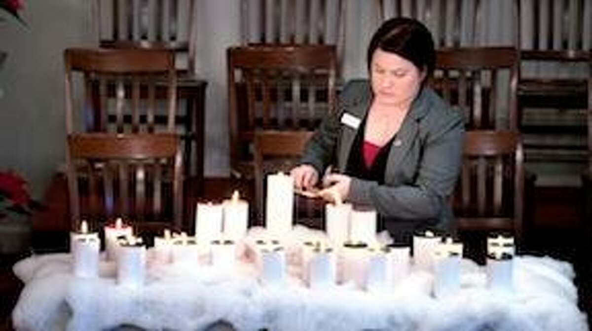 Yale Divinity School student Allysa De Wolf, Coordinator of Christian Nurture & MIssion, lights candles for the 26 victims of the Sandy Hook Elementary School shootings at the Newtown Congregational Church during worship service on Sunday morning 12/16/2012.Photo by Arnold Gold/New Haven Register