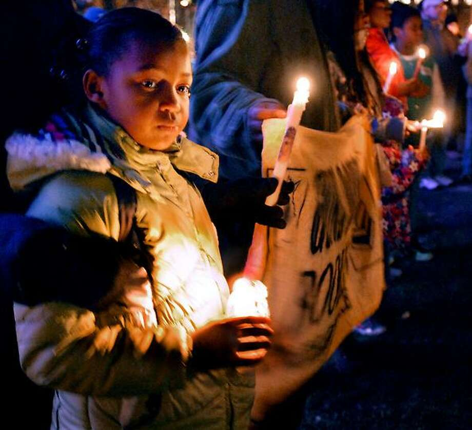 Anarea Moore,8 of New Haven, attends the candlelight vigil for victims of the shooting at Sandy Hook Elementary School. Melanie Stengel/Register