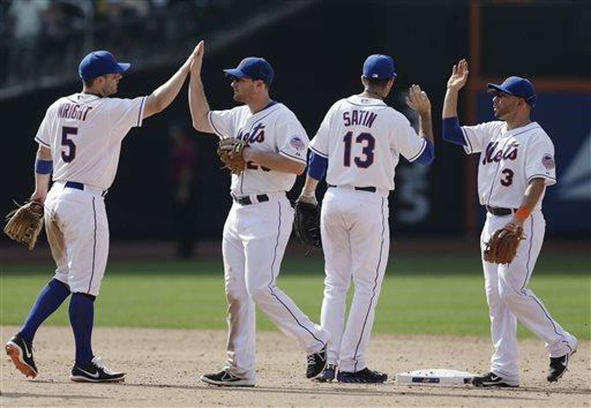 New York Mets' David Wright (5), Daniel Murphy, second from left, Josh Satin (13) and Omar Quintanilla (3) celebrate after their 5-4 win over the Philadelphia Phillies in a baseball game Saturday, July 20, 2013, in New York. (AP Photo/Frank Franklin II)