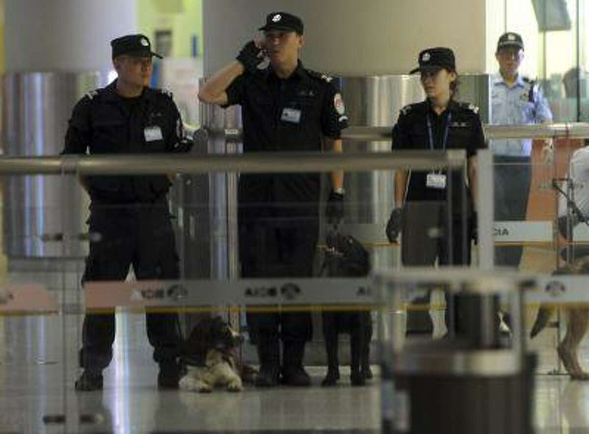 Chinese police tighten security at Beijing International Airport's Terminal 3, in Beijing, China, Saturday, July 20, 2013.
