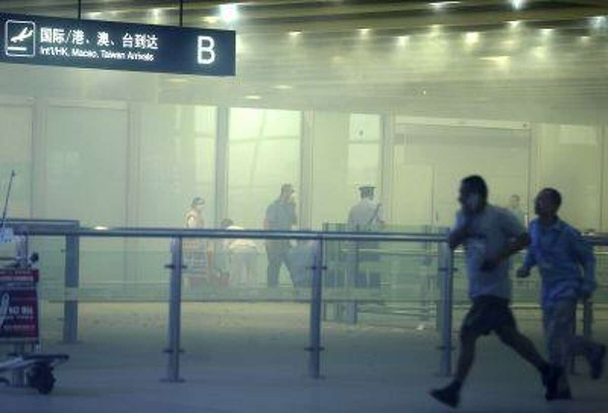 In this photo released by China's Xinhua News Agency, medical workers and policemen work at the terminal 3 of the Beijing International Airport in Beijing, Saturday, July 20, 2013.