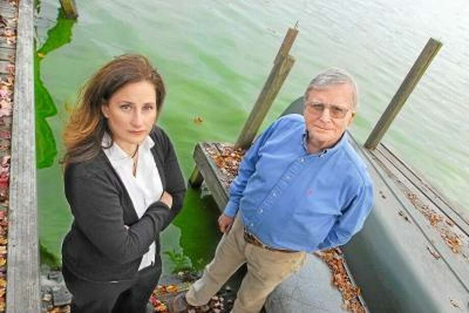 CATHERINE AVALONE/THE MIDDLETOWN PRESS Middlefield residents Amy Poturnicki, President of the Lake Beseck Association and Dick Boynton, Vice President of the LBA are seen on Boynton's dock agree the current condition of the algae in Lake Beseck may be the worse case lake residents may have seen. The association created an environmental committee to ultimately dredge the shallow areas of the lake to control the algae, curly leaf pond weed and milfoil to improve the water quality. DEEP has plans to rebuild the existing dam.