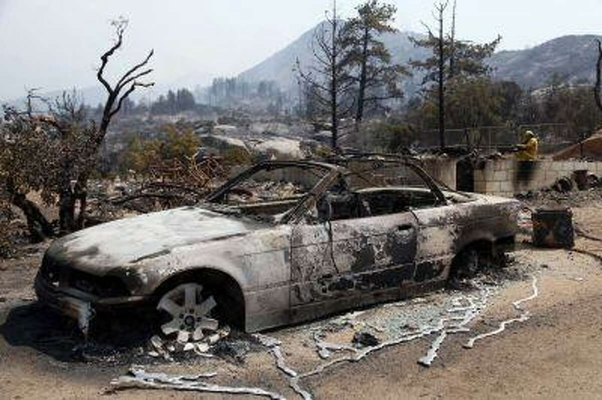 The charred remains of a car are shown after a wildfire passed through the area, Thursday July 18, 2013 in Lake Hemet, Calif.