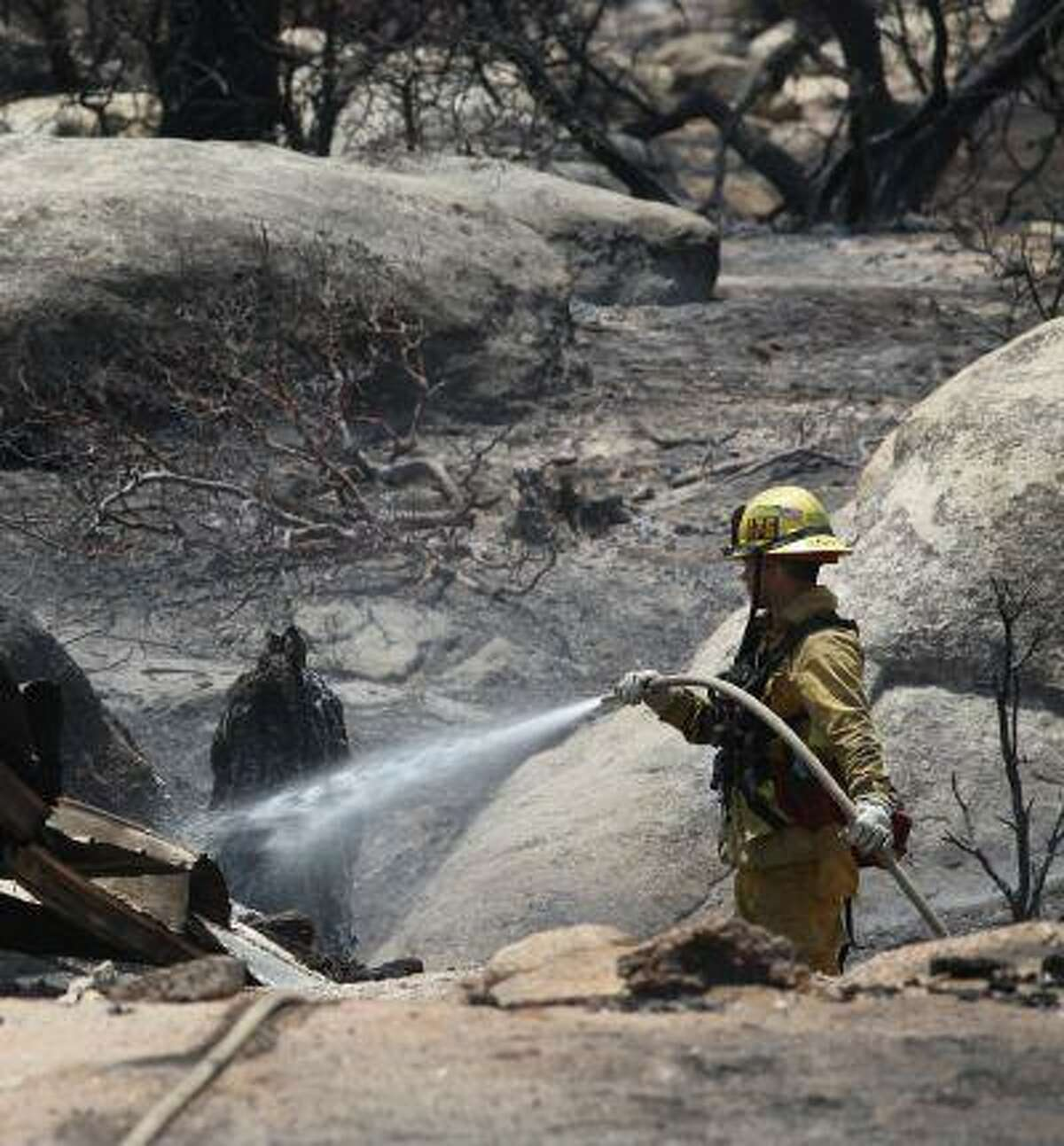 A Rancho Cucamonga firefighter mops up an area in Pine Springs Ranch in Mountain Center, Calif. Thursday, July 18, 2013, as crews continue to battle the Mountain Fire.