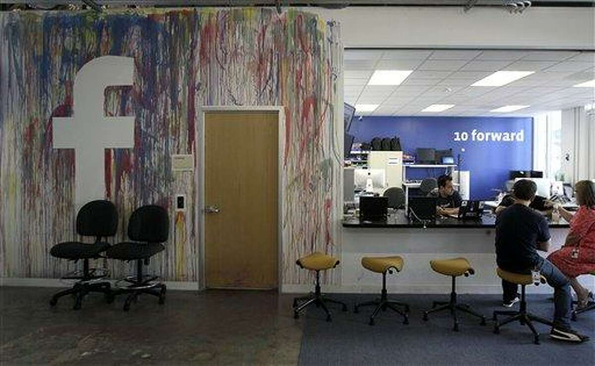 This May file photo shows workers chatting at the Facebook office in Menlo Park, Calif. (AP Photo/Jeff Chiu, File)