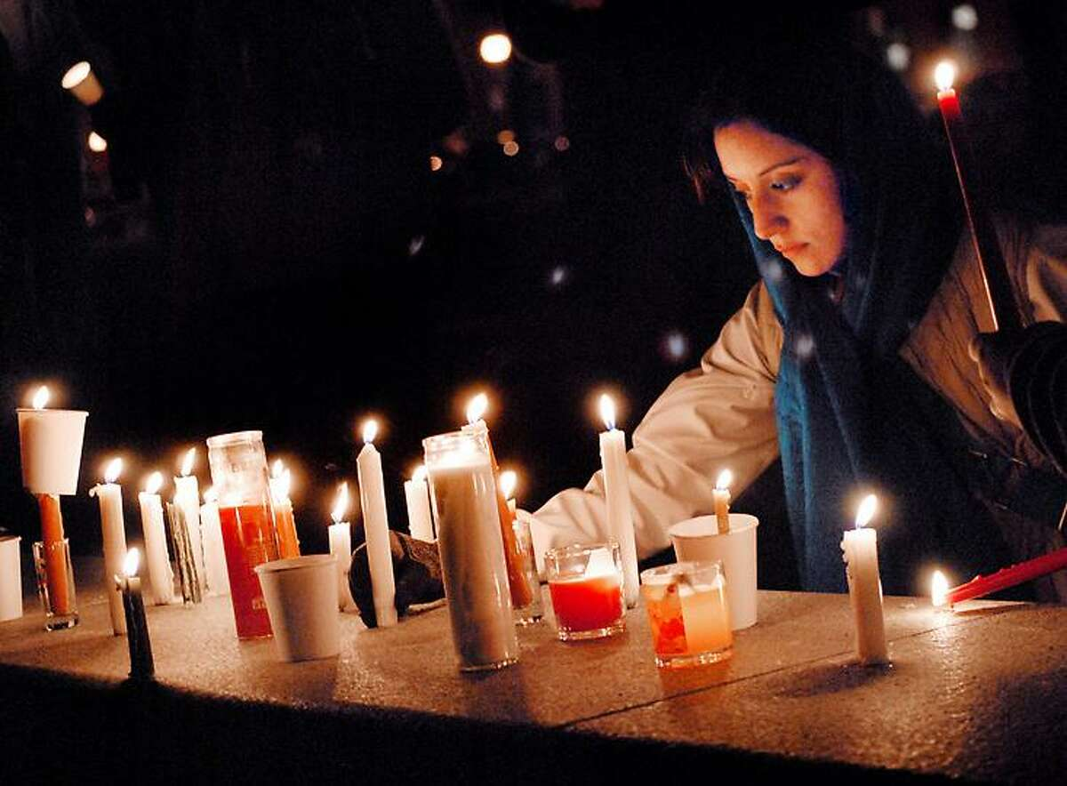 After a candlight vigil for victims of the shooting at Sandy Hook Elementary School, Lolly Berger places her candle with others on the Green. Green has a Masters of Social Work and has a web site Lovect.com Melanie Stengel/Register