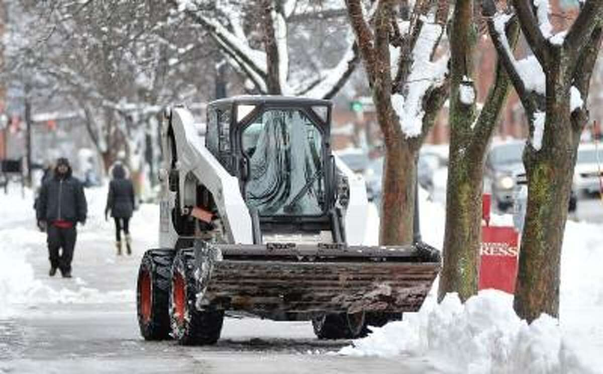 Catherine Avalone/The Middletown Press Portland resident J.T. Kelley employed by Forest City Landscaping clears the sidewalks at Metro Square on Main Street in Middletown Friday afternoon using a Bobcat S250 skid-steer.