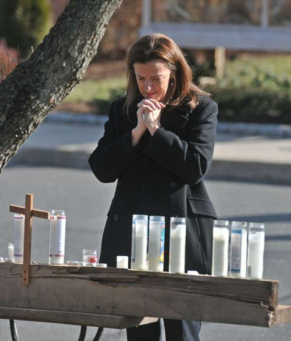 Ginny Smith of Sandy Hook prays outside the St. Rose of Lima Church in Newtown. Smith's daughter did a teaching internship recently at the Sandy Hook Elementary School and knew some of the victims. Peter Casolino/New Haven Register