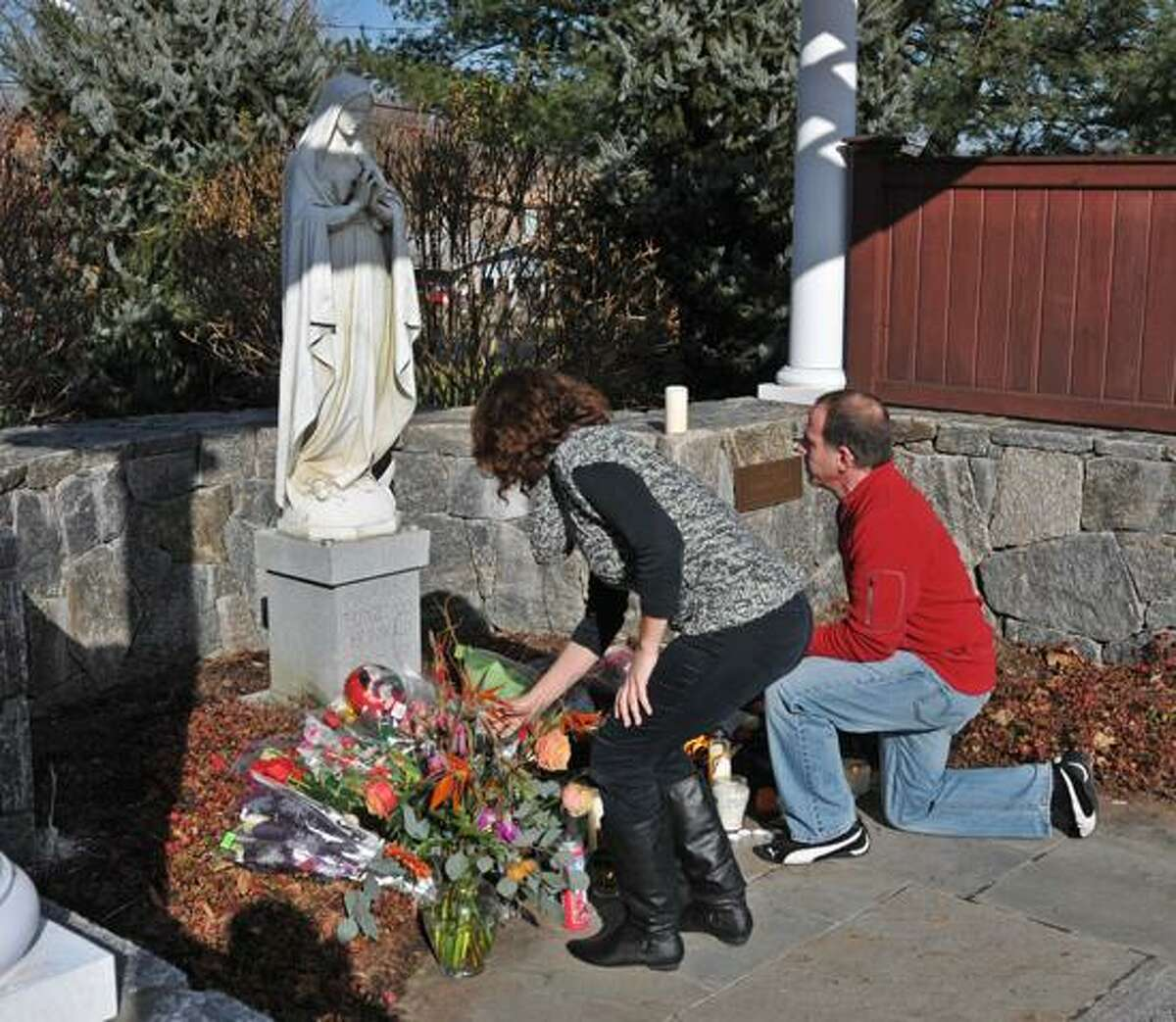 Randy and Paul Convertito of Brookfield place flowers at a statue outside the St. Rose of Lima Church in Newtown. Peter Casolino/New Haven Register