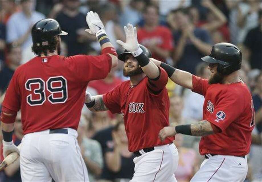 Boston Red Sox's Jonny Gomes, center, is congratulated by Jarrod Saltalamacchia, left, and Mike Napoli after his two-run home run off New York Yankees starting pitcher Andy Pettitte during the second inning of a baseball game at Fenway Park, Friday, July 19, 2013, in Boston. (AP Photo/Charles Krupa) Photo: AP / AP