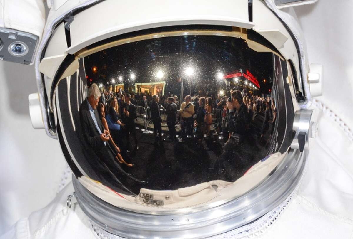"""The """"Gravity"""" premiere red carpet as seen from a reflection in an astronaut's helmet at the AMC Lincoln Square Theaters on Tuesday, Oct. 1, 2013, in New York."""