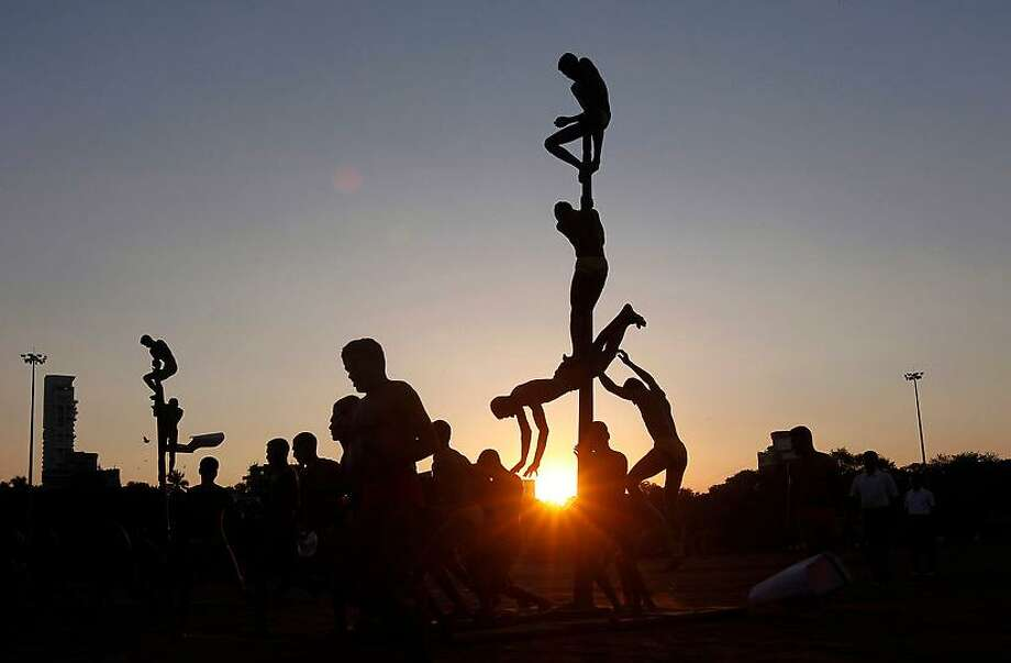 Indian army soldiers perform Mallakhamb, a traditional Indian gymnastics on a vertical wooden pole during a rehearsal for Victory Day celebrations in Mumbai, India, Thursday, Dec. 13, 2012. The Indian Army celebrates Victory Day on December 16, to commemorate its military victory over Pakistan in 1971. (AP Photo/Rajanish Kakade) Photo: ASSOCIATED PRESS / AP2012