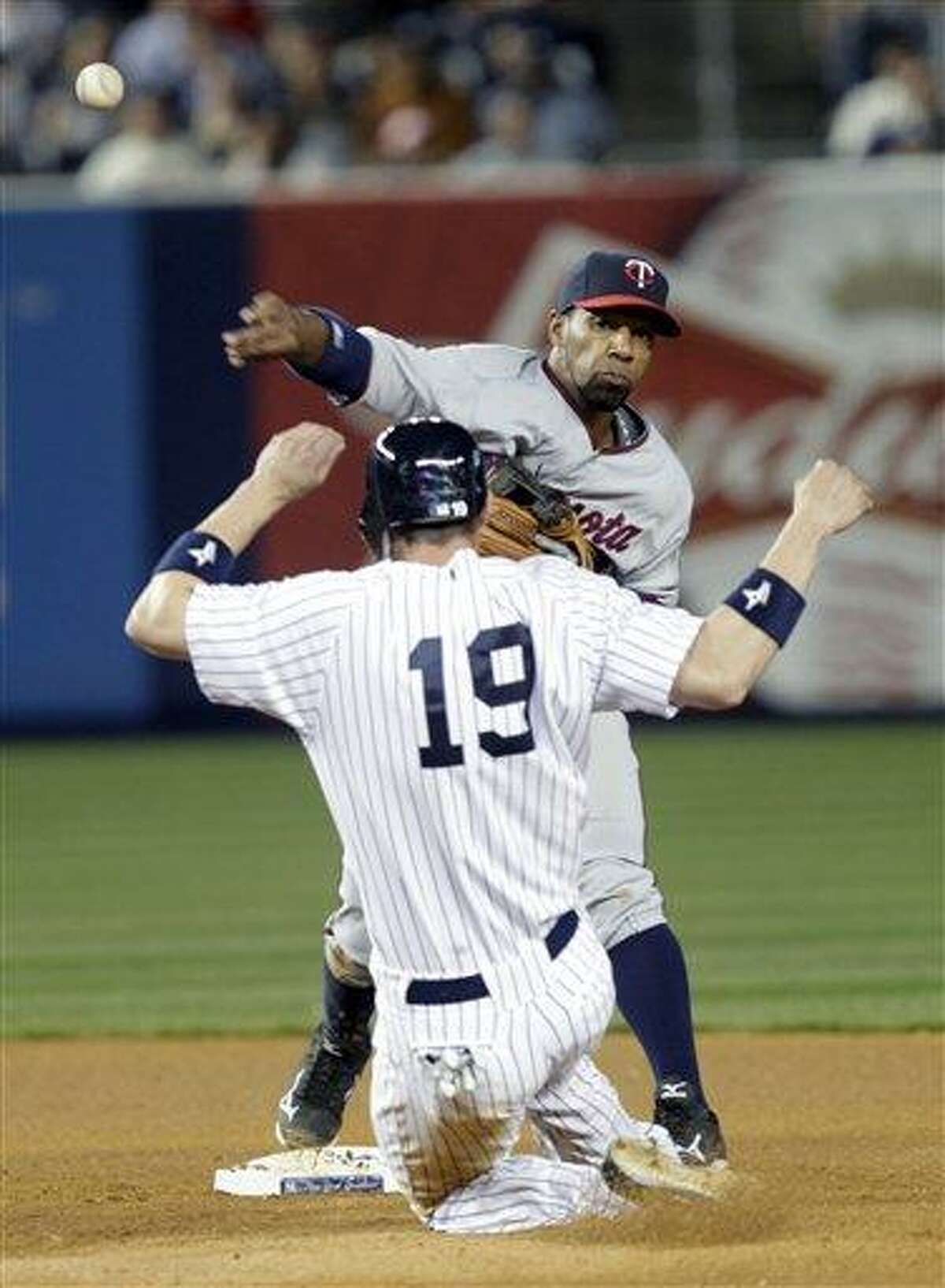 Minnesota Twins second baseman Alexi Casilla throws to first after forcing out New York Yankees' Chris Stewart during the seventh inning of a baseball game at Yankee Stadium in New York, Tuesday, April 17, 2012. Derek Jeter was safe at first. The Yankees beat the Twins 8-3. (AP Photo/Seth Wenig)