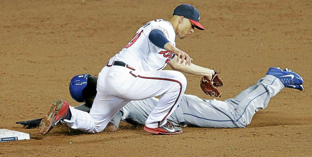The Dodgers' Dee Gordon tries to steal second base as Braves shortstop Andrelton Simmons makes the tag in the ninth inning of Game 2 of the National League division series on Friday in Atlanta. The Braves won 4-3.