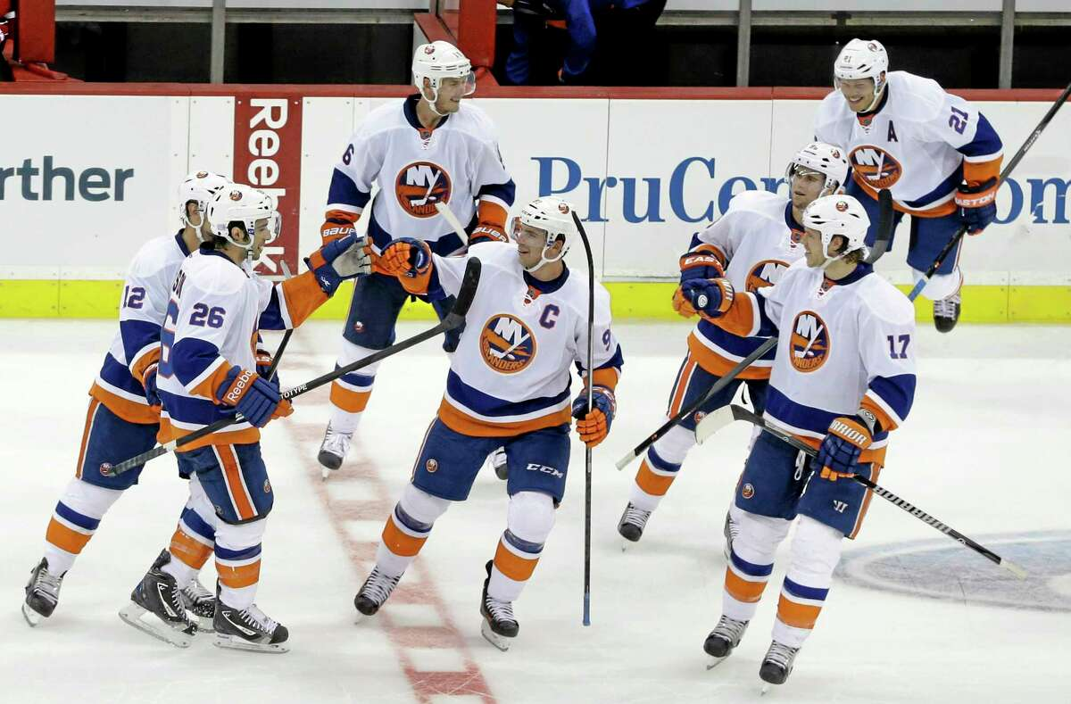 The Islanders' Matt Moulson (26) is congratulated by teammates after scoring in the shootout to give New York a 4-3 win over the New Jersey Devils on Friday in Newark, N.J.
