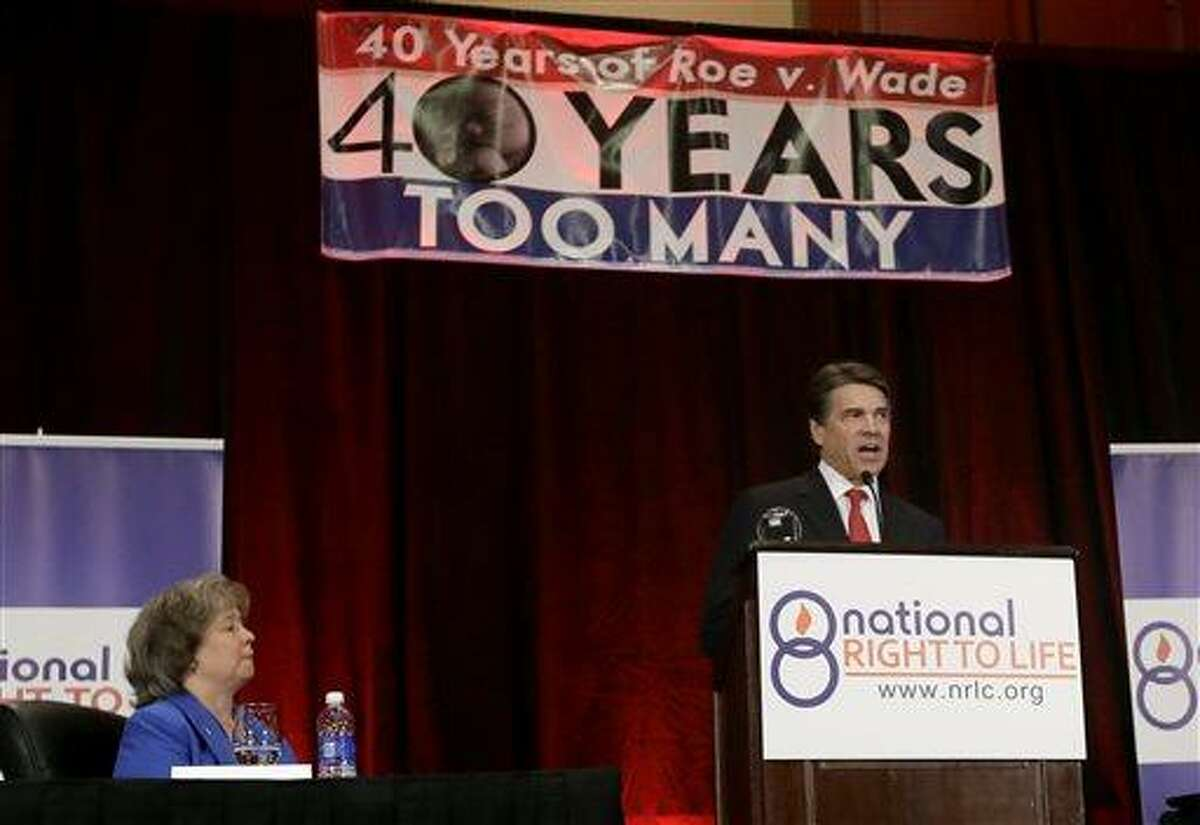 Carol Tobias, president of National Right To Life, left, watches as Gov. Rick Perry delivers a speech to a large audience in attendance at the national convention, Thursday, June 27, 2013, in Grapevine, Texas. The Republican has called a second special legislative session beginning July 1, allowing the GOP-controlled statehouse another crack at passing restrictions opponents say could shutter nearly all the abortion clinics across the country's second-largest state. (AP Photo/Tony Gutierrez)