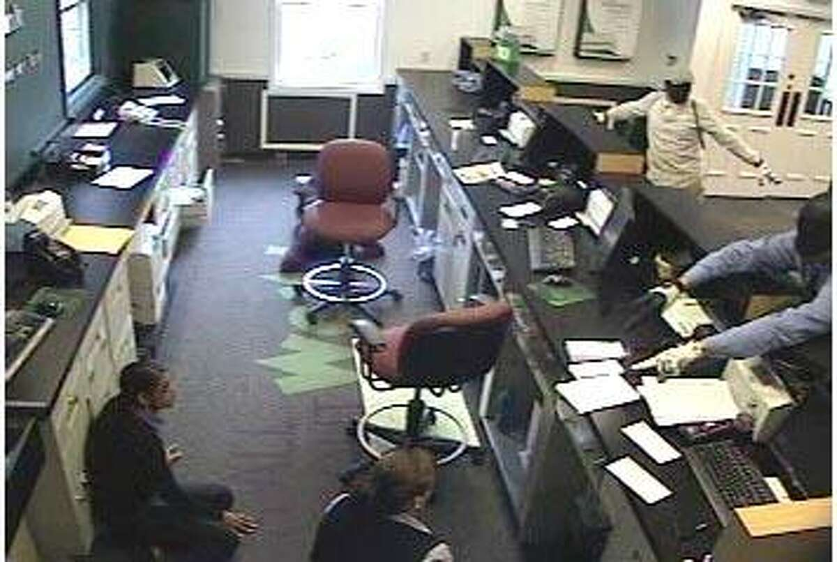 Digital video snapshot released by state police shows two suspects wearing masks and pointing handguns at tellers kneeled down at the teller line of the TD Bank North in Killingworth that was robbed Monday afternoon.