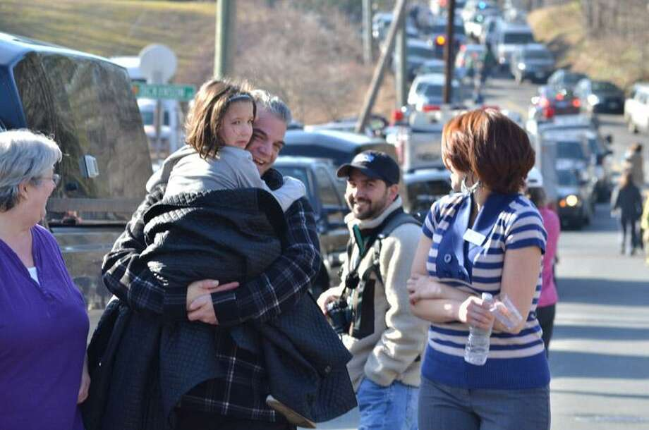 Families gather on the road leading to Sandy Hook Elementary School in Newtown after a shooting Friday morning. An official with knowledge of the shooting says 27 people are dead, including 18 children. Melanie Stengel/Register