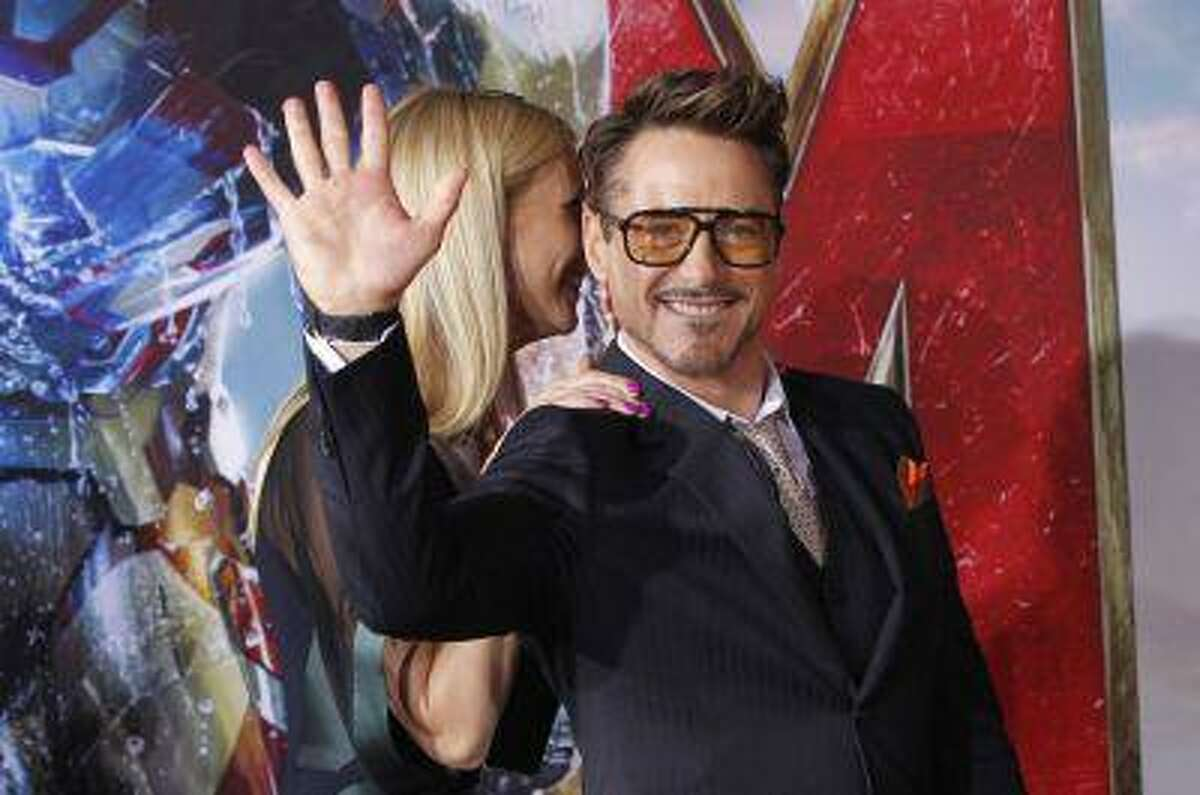 Cast member Robert Downey Jr. waves next to co-star Gwyneth Paltrow at the premiere of