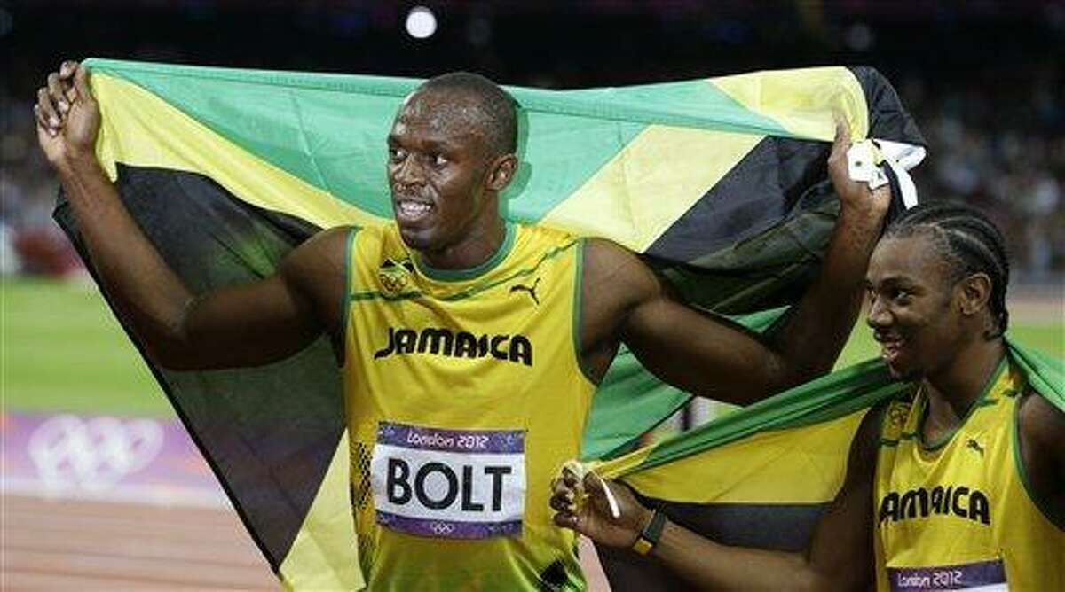 Jamaica's Usain Bolt, left, holds his national flag as teammate Yohan Blake, right, poses with him after Bolt's win in the men's 100-meter final during the athletics in the Olympic Stadium Sunday at the 2012 Summer Olympics, London. Associated Press