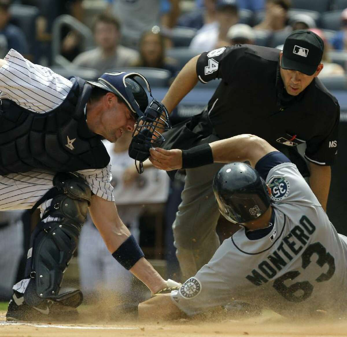 ASSOCIATED PRESS Home plate umpire Angel Campos, top right, watches as New York Yankees catcher Chris Stewart, left, tags out Seattle Mariners' Jesus Montero at the plate in the first inning of Sunday's game at Yankee Stadium in New York.