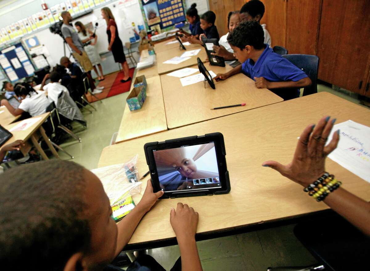 FILE- In this Aug. 27, 2013, file photo, students photograph themselves with an iPad during a class at Broadacres Elementary School in Carson, Calif. Los Angeles school officials have halted home use of iPads after nearly 300 students at Roosevelt High made quick work of hacking through security so they could surf the Internet and access social media sites. (AP Photo/Los Angeles Times, Bob Chamberlin, File)