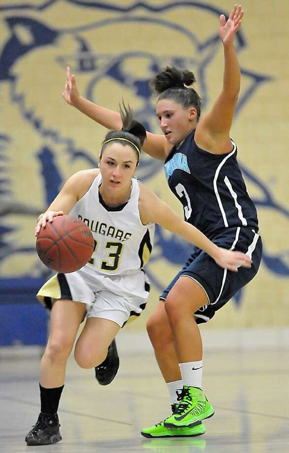 Catherine Avalone/The Middletown Press Haddam-Killingworth senior point guard Marissa Moncata drives past Ansonia senior guard Melissa Tirella Thursday night at the H-K Fieldhouse in Higganum. The H-K Cougars defeated the Ansonia Chargers 52-37 in the CIAC Class M Quarterfinal game. / TheMiddletownPress