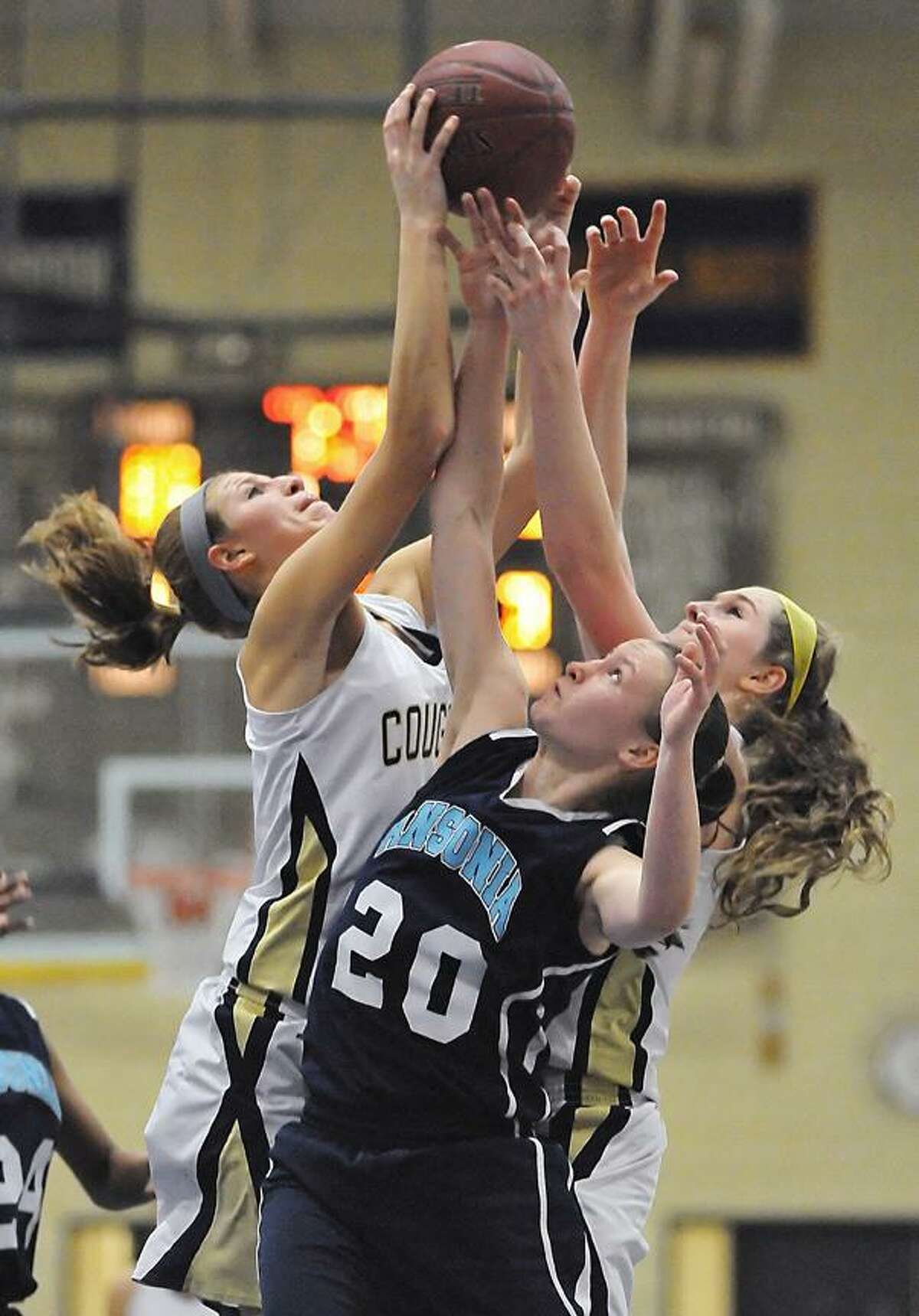 Catherine Avalone/The Middletown Press Haddam-Killingworth junior forward Kiley Anderson, at left and junior forward Lauren McCann battle Ansonia senior guard Tierney Lawlor Thursday night at the H-K Fieldhouse in Higganum. Anderson grabbed 9 rebounds and McCann pulled down 7 leading the Cougars in a 52-37 win over the Chargers in the Class M CIAC Quarterfinal game.