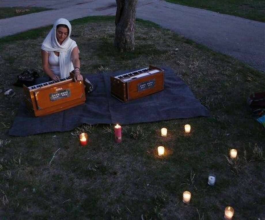 A woman plays soft music at a candle light vigil for the victims of the Sikh Temple of Wisconsin shooting in Milwaukee Sunday. Associated Press Photo: AP / FR59249 AP