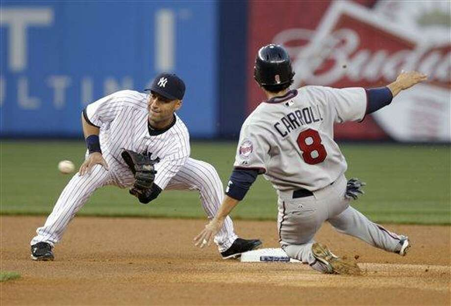 New York Yankees shortstop Derek Jeter, left, gets the ball in time to prevent Minnesota Twins' Jamey Carroll from stealing second during the first inning of a baseball game at Yankee Stadium in New York, Monday, April 16, 2012. (AP Photo/Seth Wenig) Photo: AP / AP