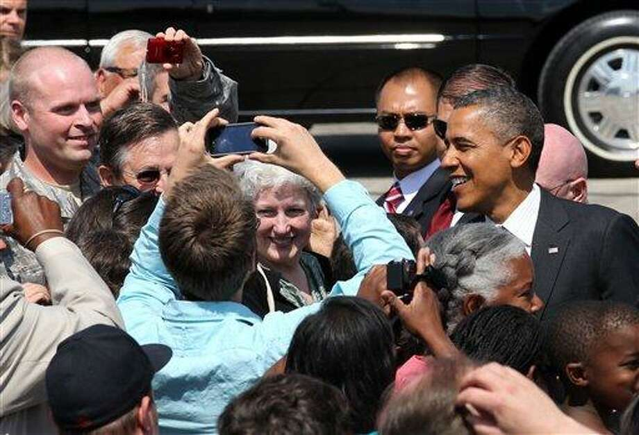 President Barack Obama greets supporters upon his arrival, Tuesday, July 24, 2012, at the 142nd Fighter Wing Oregon Air National Guard Base, in Portland, Ore. President Barack Obama has arrived in Oregon to raise money for his re-election campaign.  (AP Photo/Rick Bowmer) Photo: ASSOCIATED PRESS / AP2012
