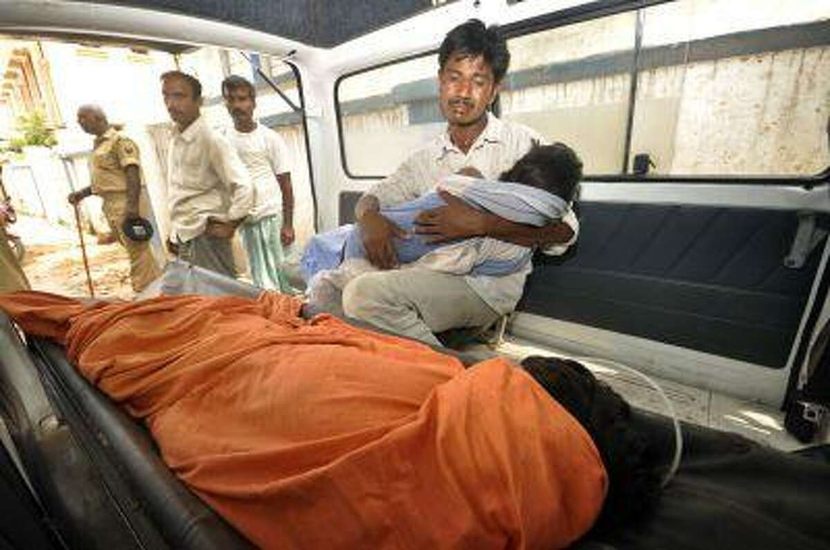 An Indian man mourns as he holds his dead daughter inside an ambulance, outside a hospital in Patna, in the eastern Indian state of Bihar, Wednesday, July 17.