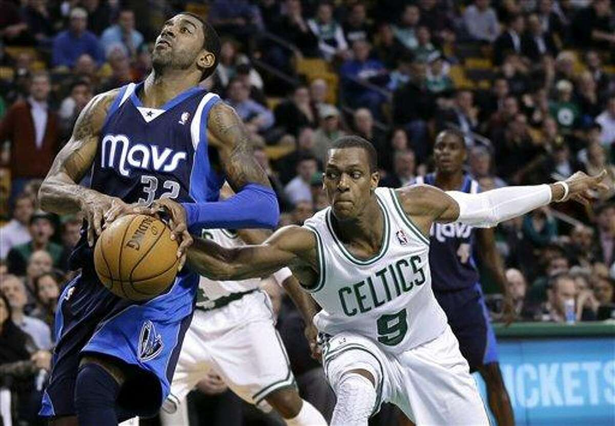 Boston Celtics guard Rajon Rondo (9) reaches for the ball as Dallas Mavericks guard O.J. Mayo (32) drives to the basket during the first overtime of an NBA basketball game in Boston, Wednesday, Dec. 12, 2012. The Celtics won 117-115 in double overtime. (AP Photo/Elise Amendola)