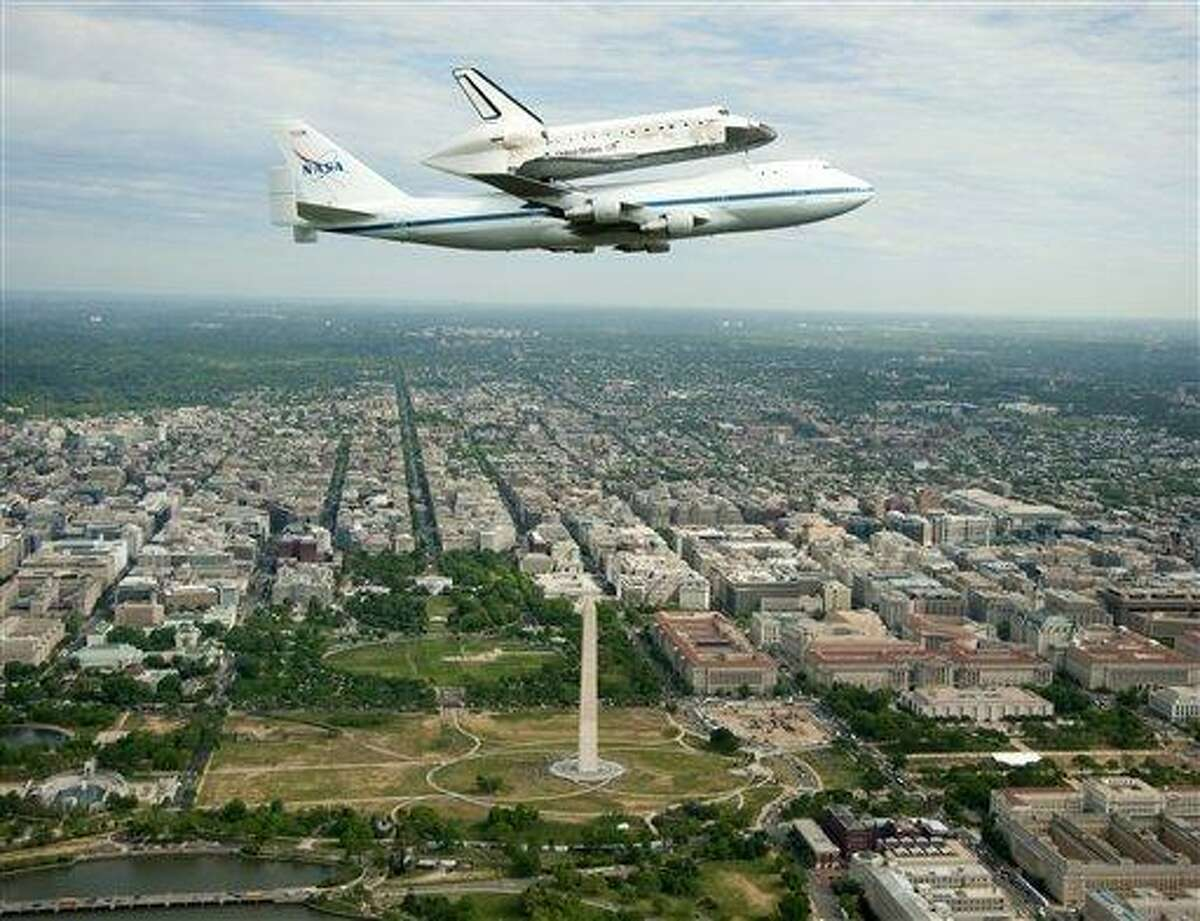 This handout photo provided by NASA shows the Space shuttle Discovery, mounted atop a NASA 747 Shuttle Carrier Aircraft, flying over Washington skyline, including the Washington Monument, as seen from a NASA T-38 aircraft, Tuesday, April 17, 2012. Discovery, the longest-serving orbiter will be placed to its new home, the Smithsonian's National Air and Space Museum's Steven F. Udvar-Hazy Center in Chantilly, Va. (AP Photo/NASA, Robert Markowitz)