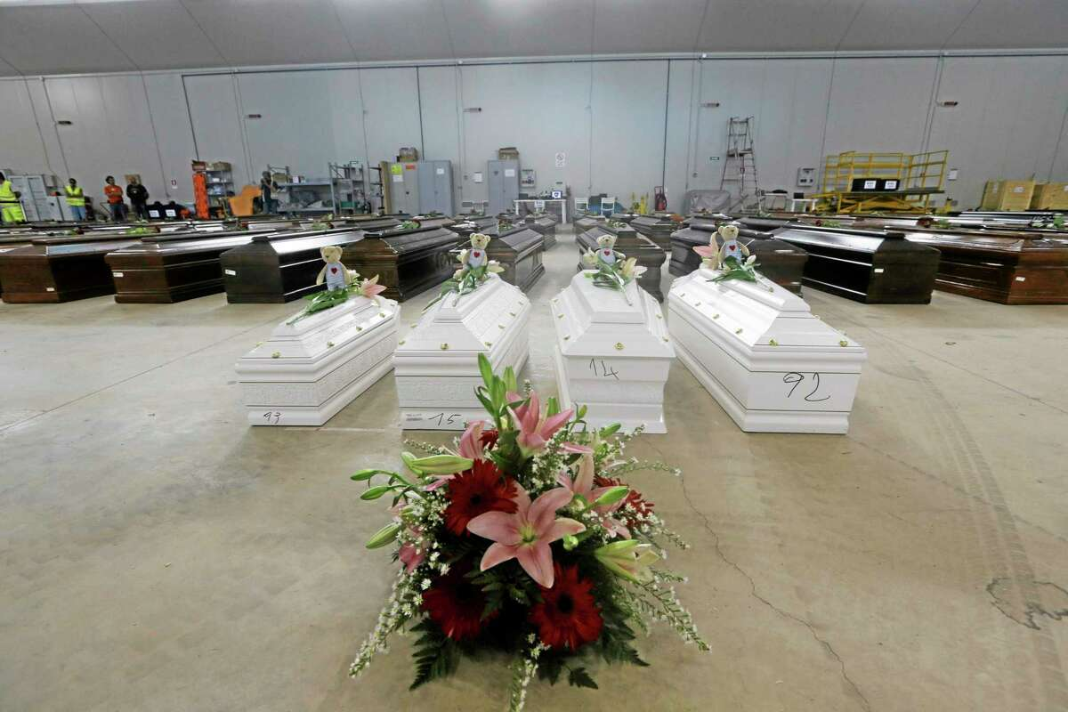 Coffins of the dead migrants are lined up inside an hangar of Lampedusa's airport, Italy, Saturday, Oct. 5, 2013. A ship carrying African migrants towards Italy sank Thursday after a fire was set onboard to attract attention of any passing boats or people on shore when they ran into trouble. They had traveled for two full days and thought they had reached safety when they saw the lights of Lampedusa. Instead, at least 111 drowned and 155 survived, some of whom were in the water for three hours, clinging to anything buoyant, even empty water bottles. (AP Photo/Luca Bruno)