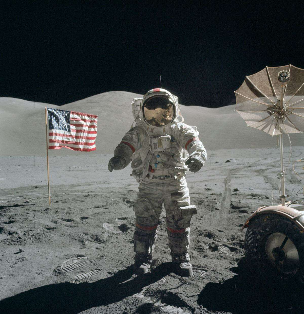 In December of 1972, Apollo 17 astronauts Eugene Cernan and Harrison Schmitt spent about 75 hours on the Moon, in the Taurus-Littrow valley, while colleague Ronald Evans orbited overhead. Near the beginning of their third and final excursion across the lunar surface, Schmitt took this picture of Cernan flanked by an American flag and their lunar rover's umbrella-shaped high-gain antenna. The prominent Sculptured Hills lie in the background while Schmitt's reflection can just be made out in Cernan's helmet. The Apollo 17 crew returned with 110 kilograms of rock and soil samples, more than from any of the other lunar landing sites. And after thirty years, Cernan and Schmitt are still the last to walk on the Moon.