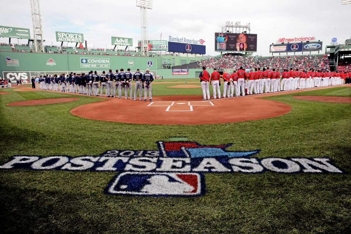 The Rays, left, and Red Sox line the baselines for the national anthem before Game 1 of baseball's American League division series Friday at Fenway Park in Boston.