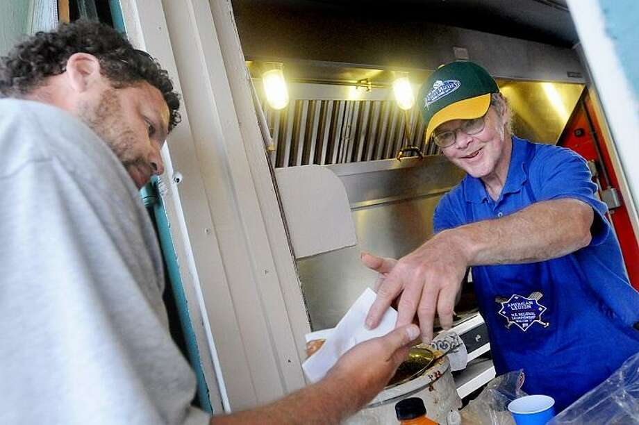 Catherine Avalone - The Middletown Press  Bob Stanley, a member of Middletown Post 75, the grillmaster at the Palmer Field concession stand delivers a hotdog to Javier Ortiz, a Middletown Park & Rec employee working at the ballpark Monday evening. Stanley has been volunteering at the stand for over 30 years. / TheMiddletownPress