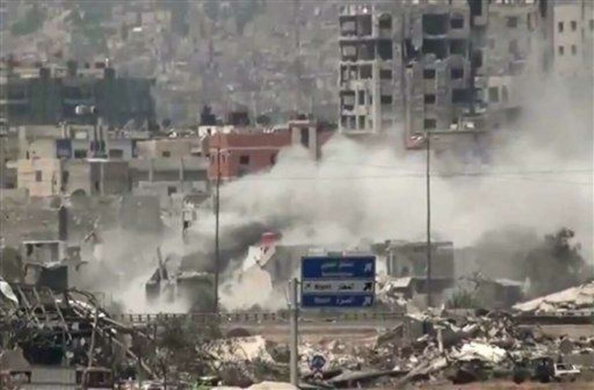 In this image taken from video obtained from Ugarit News, which has been authenticated based on its contents and other AP reporting, shows shelling of the Al-Qaboun neighborhood in rural Damascus, Syria, Monday, July 15, 2013. After seizing the momentum in recent months in Syria's civil war, President Bashar Assad's forces are on the offensive against the rebels on several fronts, including in Idlib province along the border with Turkey. Government forces are in firm control of the provincial capital of same name, while dozens of rebel brigades control the countryside.(AP Photo/Ugarit News via AP video)
