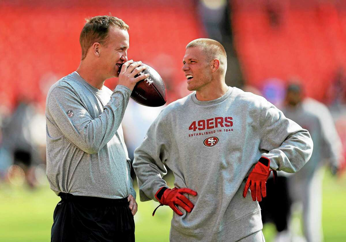Denver Broncos quarterback Peyton Manning, left, talks with then-San Francisco 49ers wide receiver Austin Collie, right, before a preseason game on Aug. 8 in San Francisco. On Thursday, Collie signed with the New England Patriots.