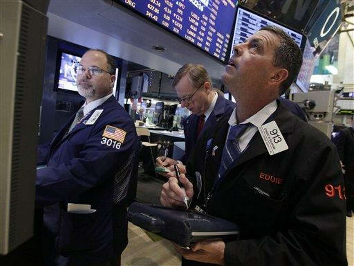 Trader Edward Baumann, right, works on the floor of the New York Stock Exchange Wednesday, June 20, 2012. Stocks edged lower early Wednesday after investors saw signs that economies could be slowing down in both the West and China. (AP Photo/Richard Drew)