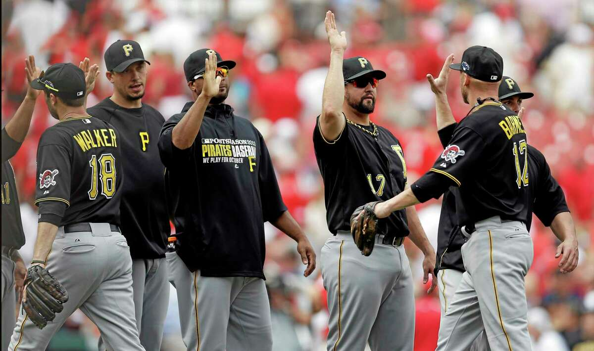 Pittsburgh Pirates players, including Neil Walker (18) and Clint Barmes (12) celebrate after beating the St. Louis Cardinals 7-1 in Game 2 of the National League division series on Friday in St. Louis. The best-of-five games series is tied at 1.