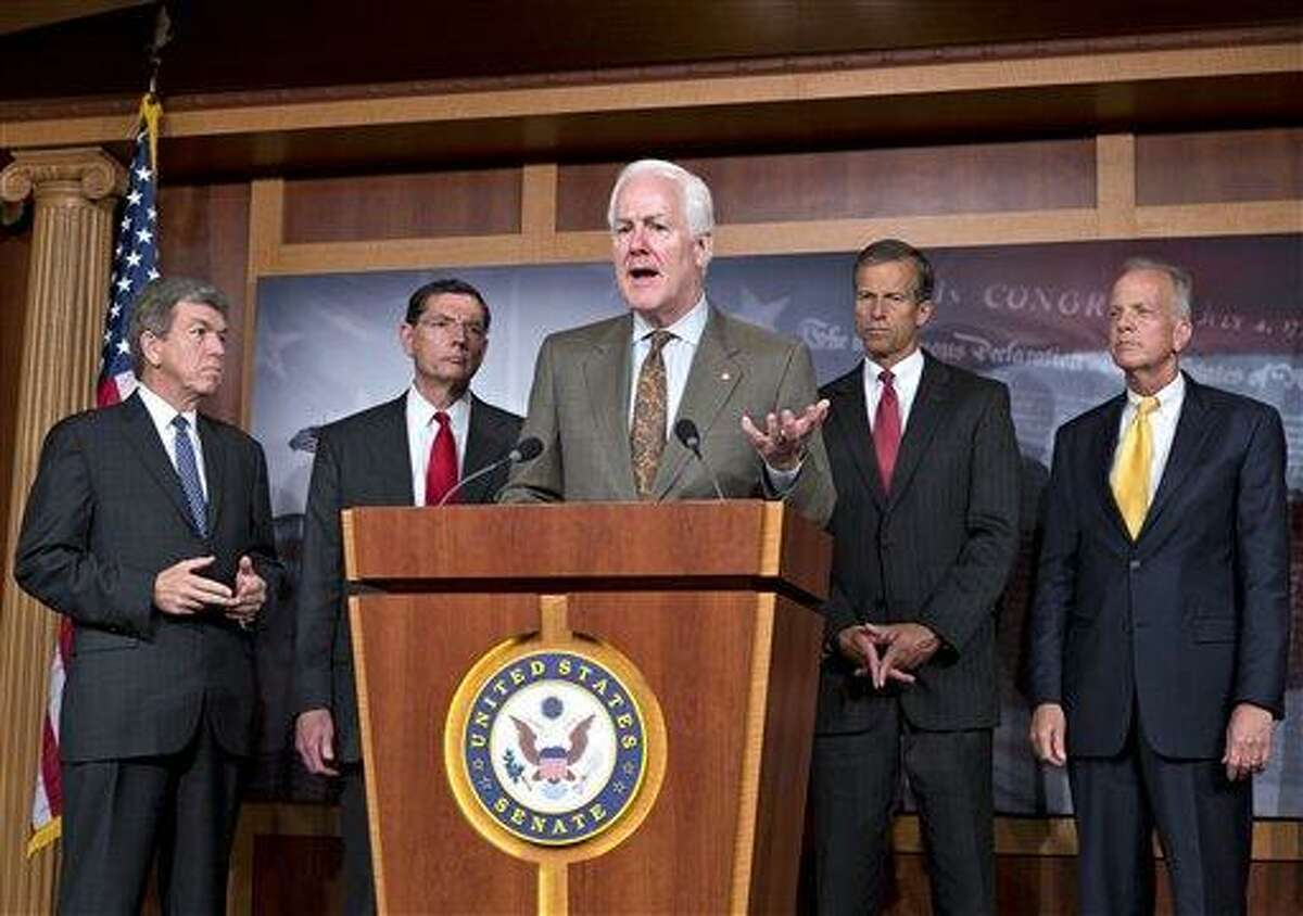 Senate Minority Whip John Cornyn, R-Texas, center, and other GOP senators, speak with reporters at the Capitol about the Affordable Care Act, popularly known as