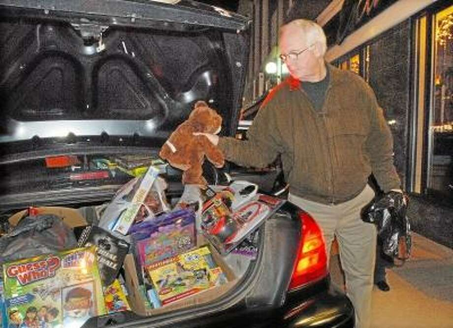 """Middlefield resident Tom Cady and his wife Gini, not pictured dropped off a Mary Meyer Big Brown Bear for the """"Stuff a Cruiser"""" toy drive after enjoying dinner on Main Street in Middletown Thursday night. Catherine Avalone/The Middletown Press"""