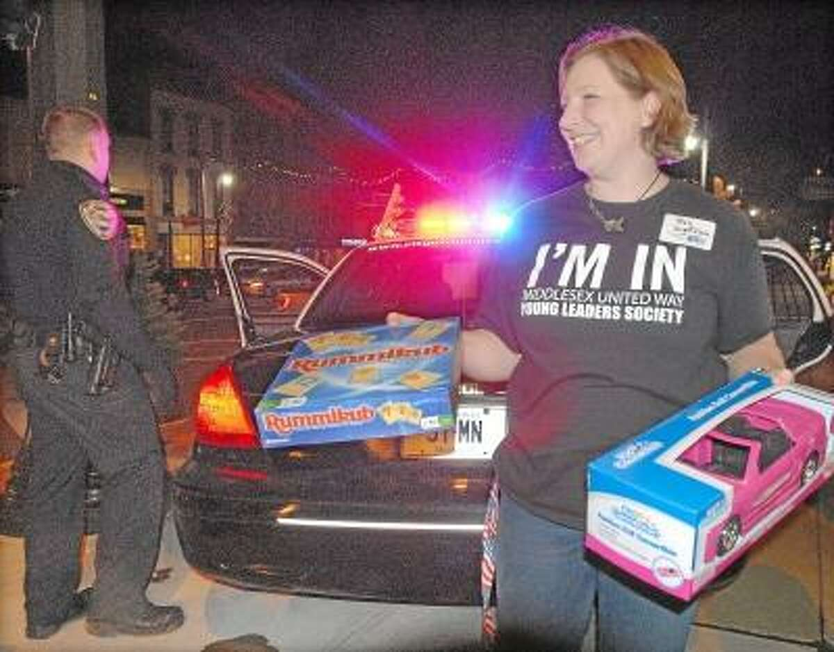 """East Hampton resident Meg Slater, a member of the steering commitee for the Middlesex United Way's Young Leader Society removes toys from the back seat of a city police vehicle collected Thursday night during the """"Stuff a Cruiser"""" toy drive on Main Street. Catherine Avalone/The Middletown Press"""