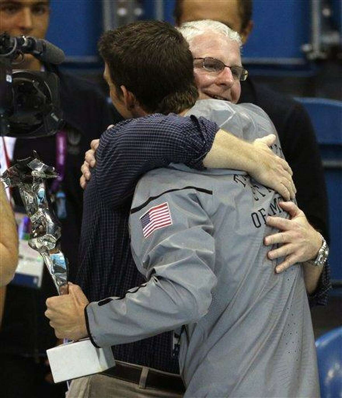 United States' Michael Phelps receives a hug from his coach Bob Bowman as he holds a trophy for the most decorated olympian at the Aquatics Centre in the Olympic Park during the 2012 Summer Olympics in London, Saturday, Aug. 4, 2012. Bob Bowman has been there every step of the way for Michael Phelps -- through all the gold medals, world records, championships and, yes, even the occasional missteps. (AP Photo/Michael Sohn)