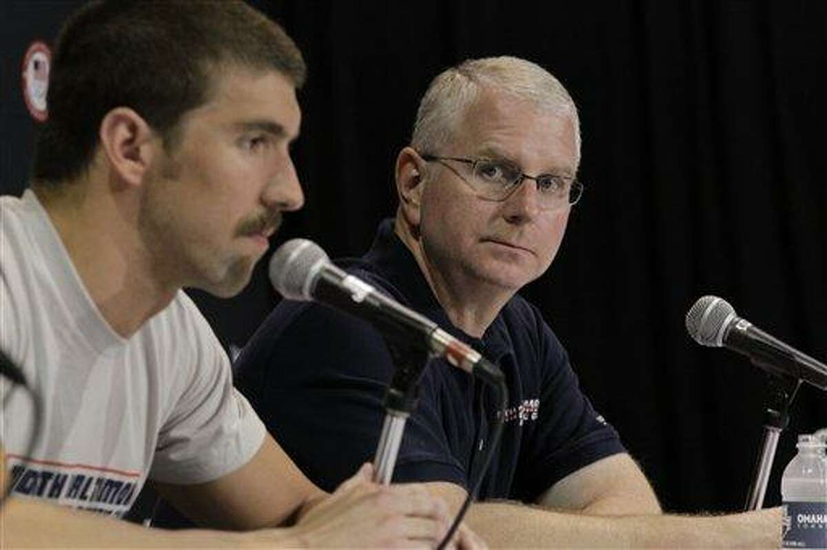 FILE - In this Saturday, June 23, 2012 file photo, Michael Phelps' coach Bob Bowman, right, listens as Phelps speaks during a news conference at the U.S. Olympic swimming trials in Omaha, Neb. Bowman has been there every step of the way for Phelps -- through all the gold medals, world records, championships and, yes, even the occasional missteps. They forged one of the most unique relationships in all of sports, a coach who took the child of recently divorced parents under his wing at age 11 and nurtured him to greatness in the pool. (AP Photo/Mark Humphrey, File)